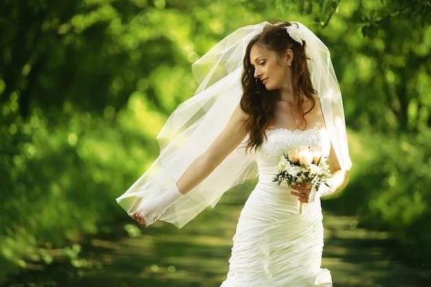 Belle mariée dans la robe de mariée dans la nature