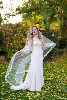 Belle mariée dans une robe de mariée redresse le voile