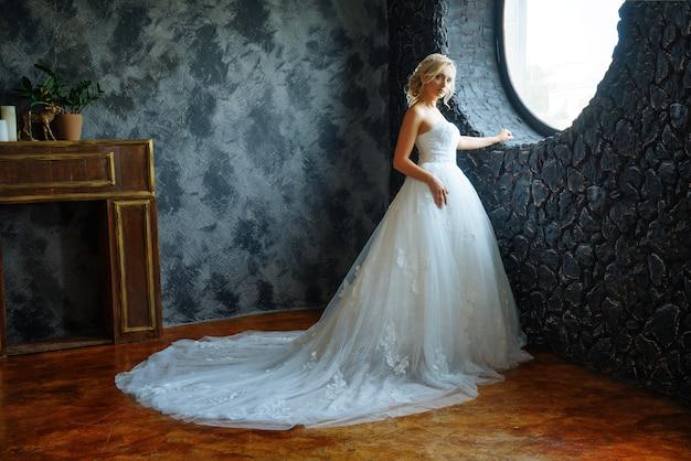 Une belle mariée dans une très belle robe longue avec un train se tient près de la fenêtre.