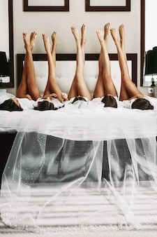 Belle mariée & demoiselles d'honneur montrant des jambes sexy sur le lit