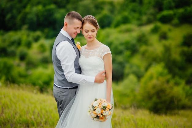 Belle mariée et élégant marié marchant après la cérémonie de mariage.