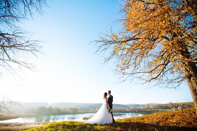 Belle mariée élégante heureuse avec un marié élégant dans la nature