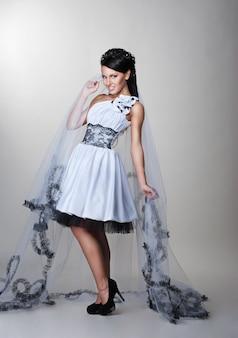 Belle mariée est debout en robe de mariée sur fond gris