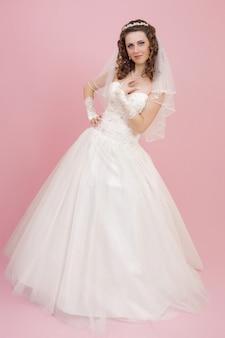 Belle mariée est debout en robe de mariée