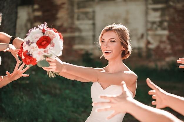 Belle mariée jette un bouquet de mariée à ses amis. vacances et traditions