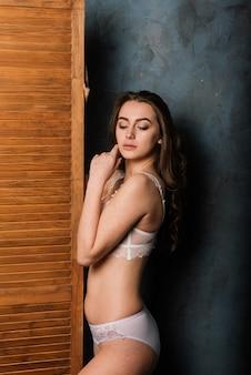 Belle mariée en lingerie blanche assise dans sa chambre