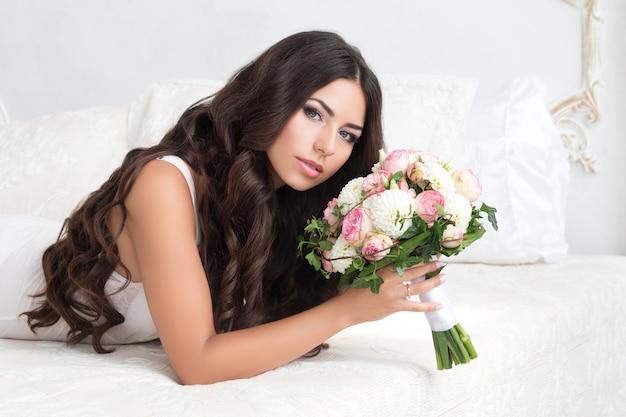 Belle mariée en lingerie blanche tenant le bouquet nuptial pose sur le lit