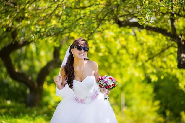 Belle mariée à lunettes de soleil posant dans le parc