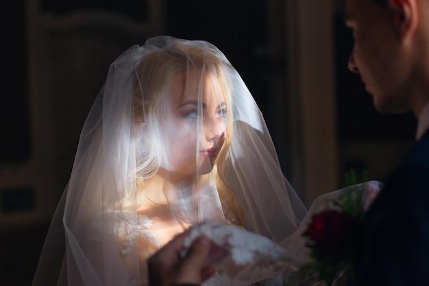 Belle mariée avec un maquillage chic recouvert de voile de mariage et regarde le marié