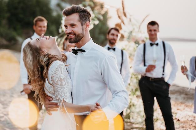 Belle mariée et le marié ayant leur mariage avec des invités sur une plage