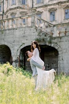 Belle mariée et le marié chinois magnifiques marchant en journée ensoleillée et s'embrassant.