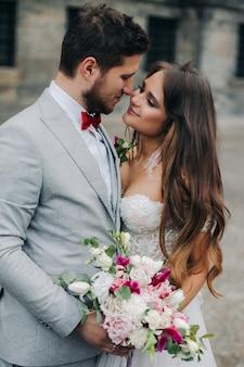 Belle mariée et le marié embrassant et s'embrassant le jour de leur mariage en plein air