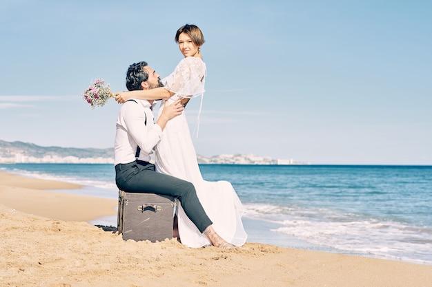 Belle mariée et le marié sur la plage se regardant avec beaucoup d'amour et de joie
