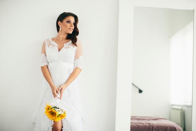 Belle mariée posant dans une robe de mariée et tenant un bouquet de tournesol