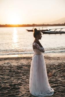 Belle mariée posant sur la plage derrière la mer au coucher du soleil