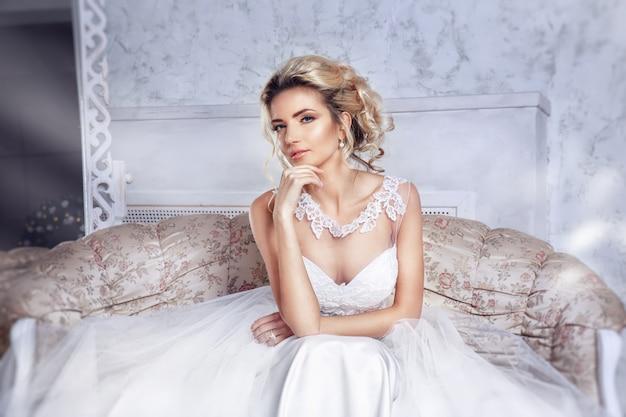 Belle mariée posant en robe de mariée assise sur un canapé dans un blanc.