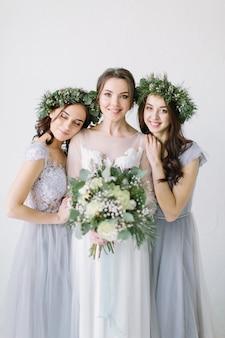 Belle mariée riante dans une robe de mariée blanche tenant un bouquet de demoiselles d'honneur en robes et couronnes bleu gris