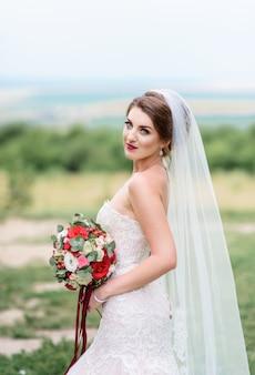 Belle mariée en robe blanche chic pose avec bouquet de mariage rouge sur une pelouse verte