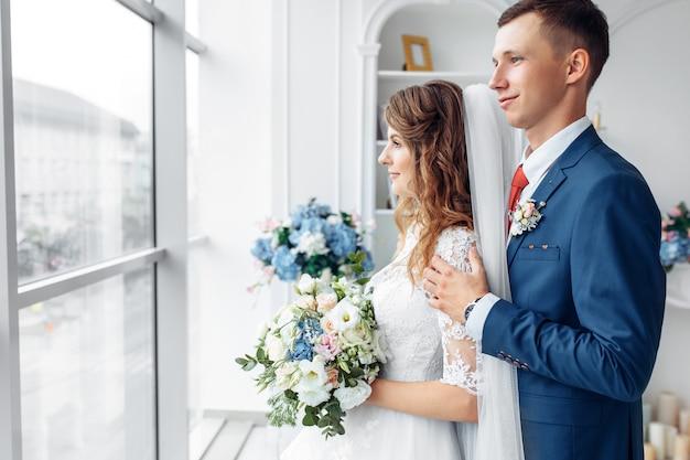 Belle mariée en robe blanche et le marié en costume, posant en intérieur studio blanc, mariage