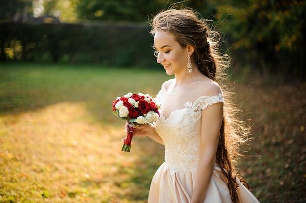 Belle mariée en robe blanche tenant un beau bouquet de roses rouges dans le parc verdoyant. conception du mariage
