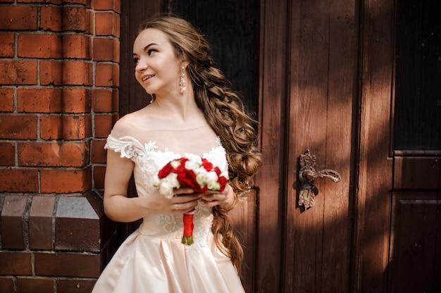 Belle mariée en robe de mariée blanche avec un bouquet de mariage debout près de la porte en bois de l'ancien bâtiment