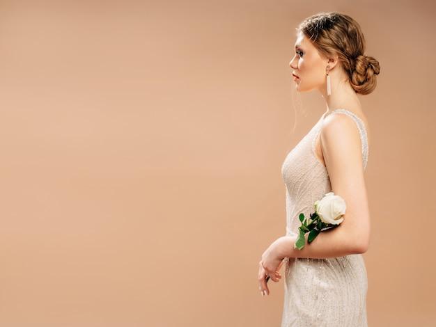 Belle mariée en robe de mariée brillante avec une rose blanche dans ses mains.