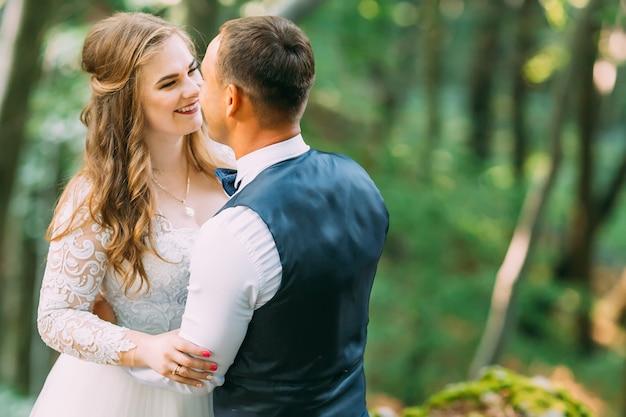 Belle mariée en robe de mariée et les jeunes mariés de maquillage doux étreignant dans la forêt