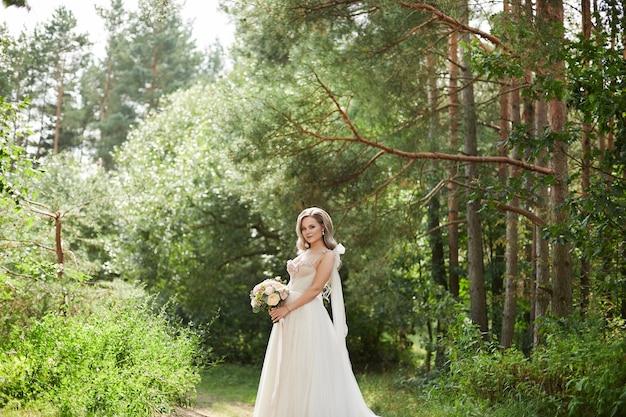 Belle mariée en robe de mariée de luxe en gardant le bouquet en marchant dans le parc