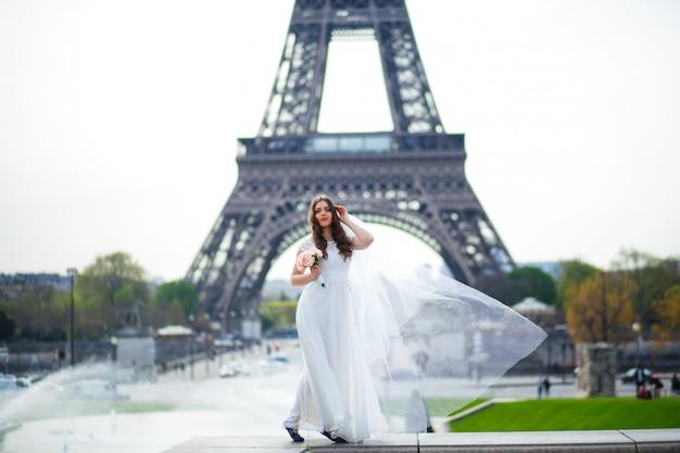 Belle mariée en robe de mariée riche tourbillonne sur la place devant la tour eiffel