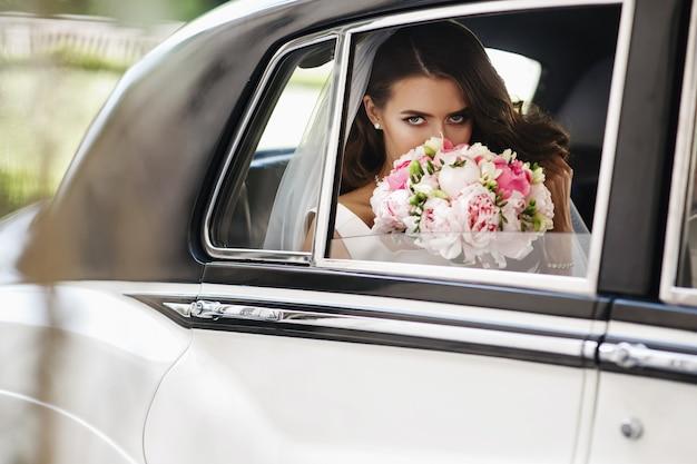 Belle mariée s'assoit avec bouquet de mariage dans une voiture rétro et s'amuse