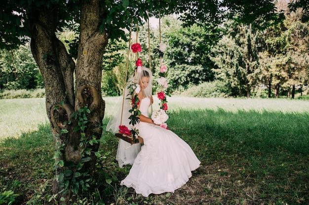 Belle mariée se balancer sur une balançoire