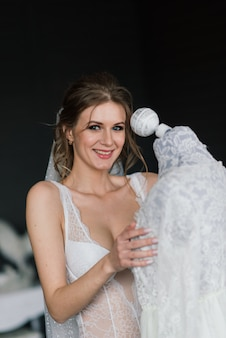 Belle mariée sexy en lingerie blanche allongée sur le lit dans sa chambre
