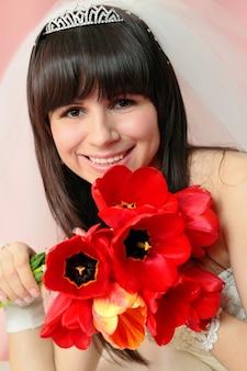 Belle mariée souriante avec le bouquet de tulipes rouges