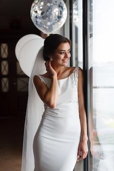 Belle mariée souriante en robe de mariée fashion intérieure près de la fenêtre