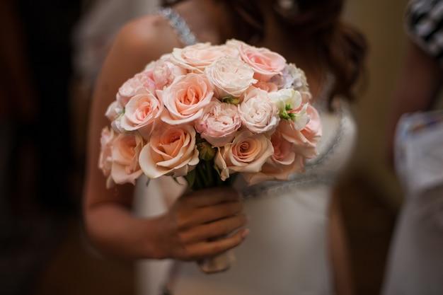Belle mariée tenant des roses roses bouquet closeup