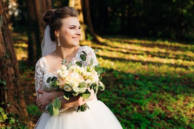 Belle mariée tient le bouquet de mariage et souriant mignon dans le parc
