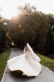 Belle mariée tourbillonne sur un chemin
