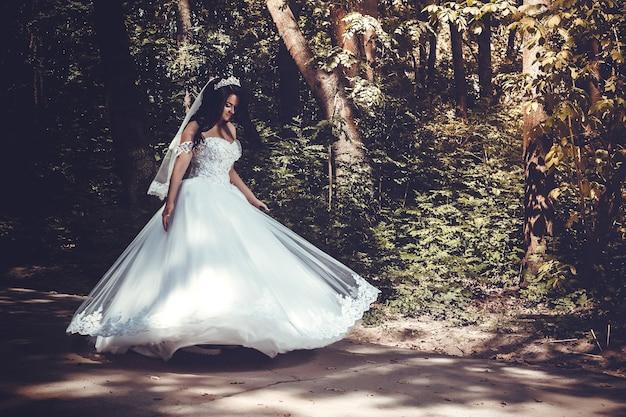 Une belle mariée tourbillonne dans une robe de mariée somptueuse au milieu du parc, image tonique