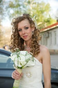 Belle mariée vêtue d'une robe blanche avec un bouquet de lys calla
