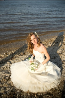 Belle mariée vêtue d'une robe blanche sur la côte de la rivière en été maquillage et coiffure professionnels