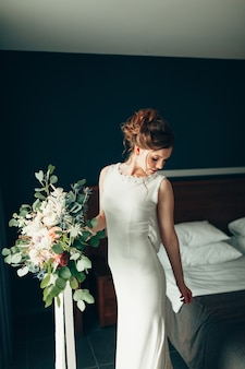 Belle mariée vêtue d'une robe en dentelle blanche avec un bouquet de fleurs se retourne et regarde