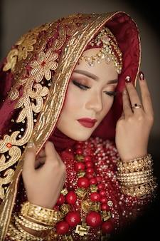 Belle mariée vêtue d'une robe rouge et or