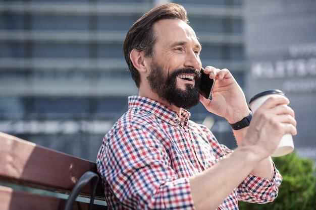 Belle matinée. enthousiaste bel homme parlant au téléphone tout en buvant du café