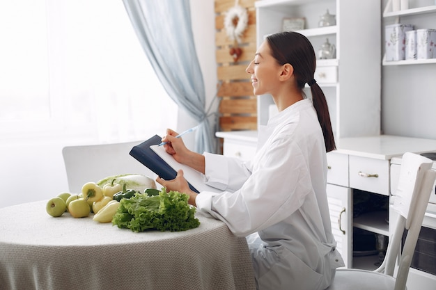 Belle médecin dans une cuisine avec des légumes