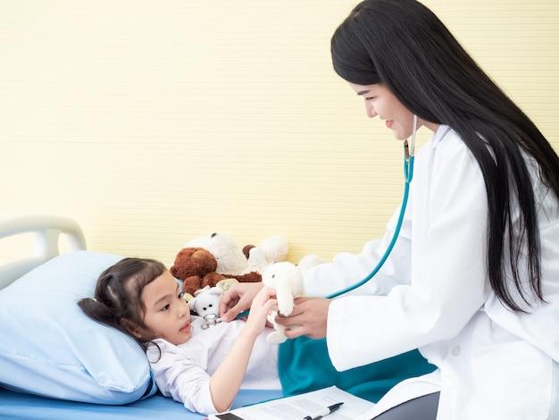 Belle médecin examinant une petite fille avec un stéthoscope usagé pour écouter à la poitrine et donner une poupée à l'enfant.