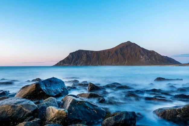 Belle mer bleue avec magnifique montagne dans les lofoten au coucher du soleil