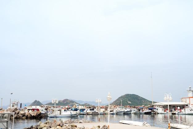 Belle mer, ciel, nuages et un bateau au port de turgutreis à bodrum,