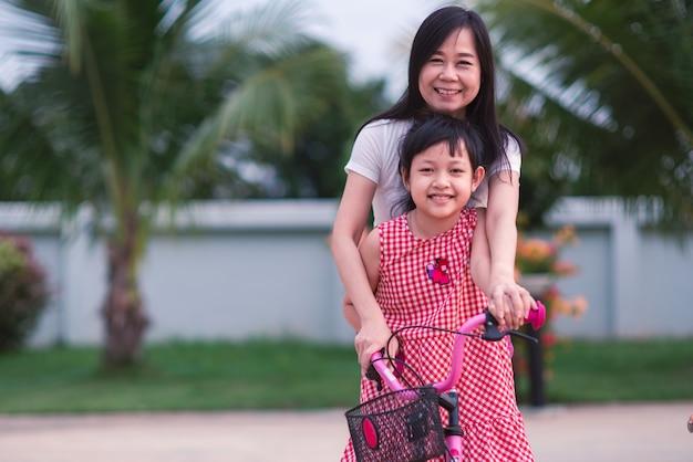 Belle mère asiatique enseignant et étreignant sa fille pour faire du vélo avec le sourire et heureux