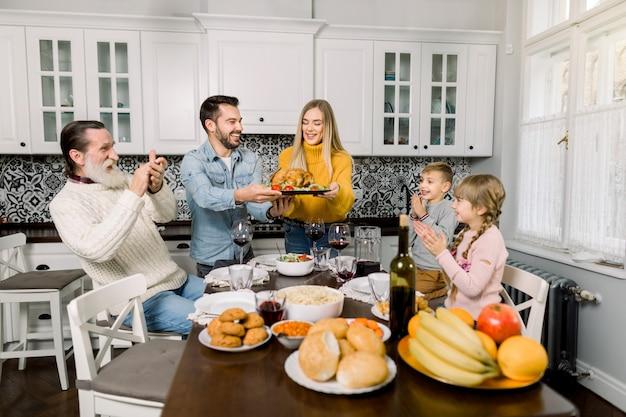 Belle mère et beau père portant la dinde pour la famille sur le dîner de thanksgiving. vieux grand-père et enfants assis à la table
