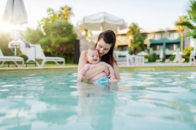 Belle mère caucasienne debout dans la piscine et tenant son fils de 6 mois. bébé appréciant et souriant.